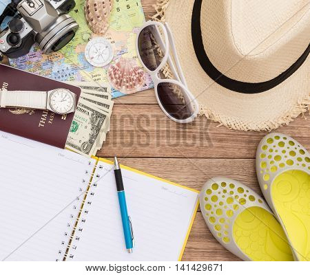 Travel concept with digital camera straw hat sunglasses world map compass passport money wristwatch shoes notepad pen and seashell on wooden table