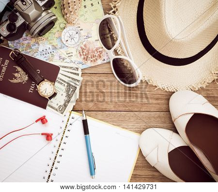 Travel concept with digital camera straw hat sunglasses world map compass passport money wristwatch earphones shoes notepad pen and seashell on wooden table