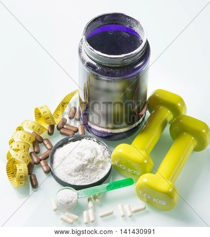 big set of sports nutrition with capsules and a white powder on the glass table