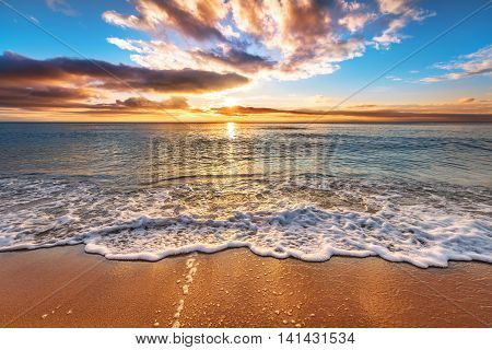Colorful ocean beach sunrise. Golden sands and blue sky.