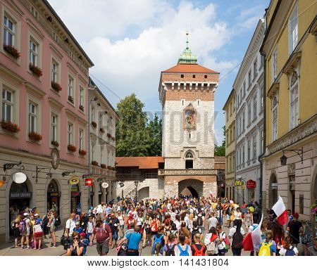 KRAKOW, POLAND - JULY 29, 2016: World Youth Day 2016. Crowd of young pilgrims at Gothic St Florian's Gate (Brama Florianska) in Cracow, Poland
