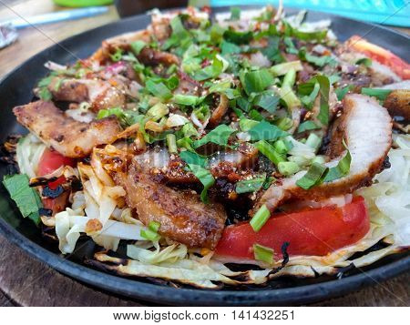 Spicy charcoal-boiled pork neck in hot plate Spicy grilled pork in Thai style.
