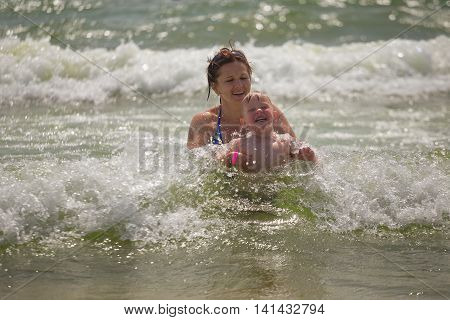 Mother giving son a swimming lesson in Sea with waves during summer.
