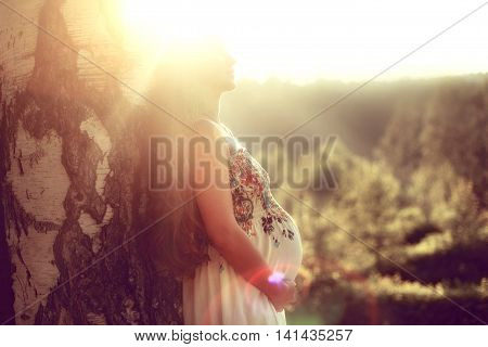 Pregnant woman with long hair standing in the summer against a tree in the rays of the setting sun and holding his stomach with his hands enjoying the nature