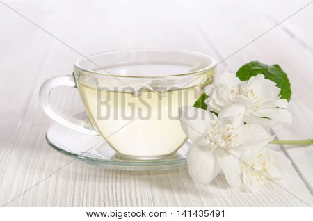 Glass cup of tea with jasmine on the white background
