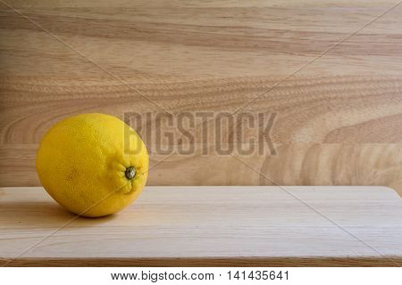 One lemon on wooden background. Contains vitamins. Useful for colds.