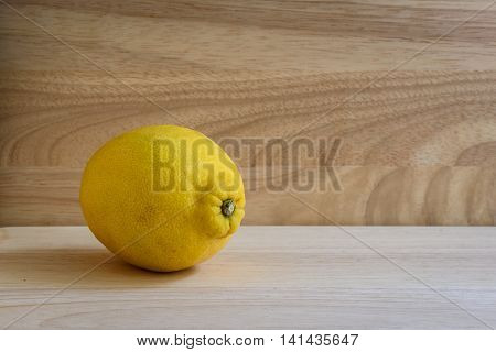 One ripe lemon on wooden background. Contains vitamins. Useful for colds.