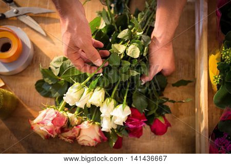 Male florist preparing flower bouquet at his flower shop