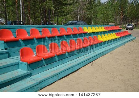 A number of multi-colored seats for spectators under open sky