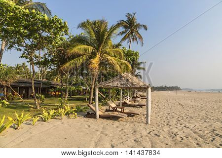 Coconut palm leafs on a perfect beach and sun beds for tourists. Concept travel and holiday in Asia Myanmar