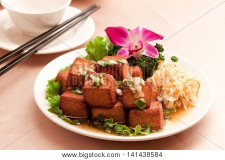 Fried tofu with lettuce and salad on white plate