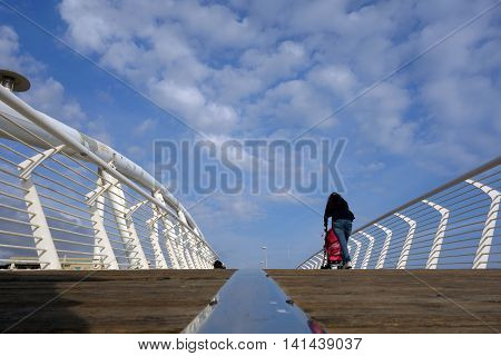 LADISPOLI ITALY - JUNE 9 2016: people walk over the Pedestrian modern Bridge enjoying the seaside