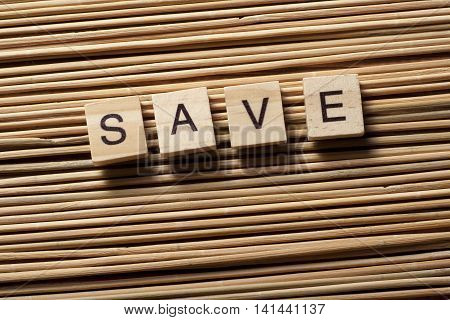 SAVE word written on wood block. Wooden abc.