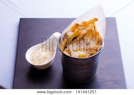 Snacks truffle sauce cheese fries potato on black plate