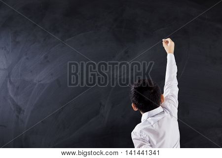 Male elementary school student using a chalk to write or drawing on the empty blackboard