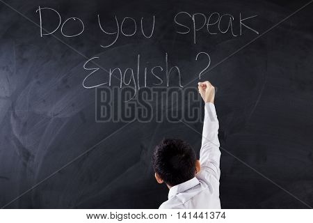 Little boy using a chalk to write text Do You Speak English on the chalkboard shot in the class