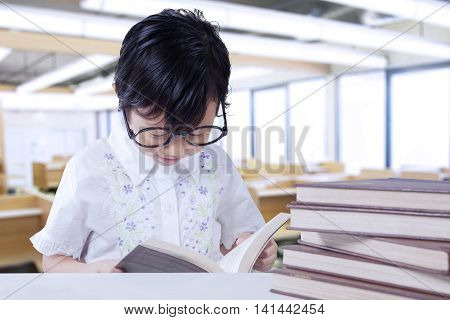 Portrait of a clever little girl reading book on the table in the classroom