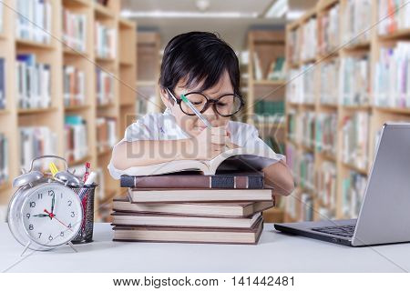Portrait of a clever little girl learns in the library while writing on the book with laptop and alarm clock on the table