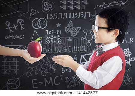 Portrait of a little boy receiving a red apple from someone in the classroom with doodles on the chalkboard