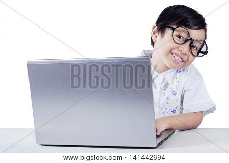 Cute female elementary school student looking and smiling at the camera while using laptop on the table isolated on white background