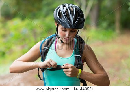 Female athletic tying backpack strap in forest