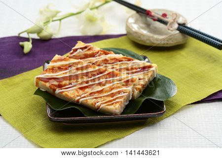 Real firmer okonomiyaki on green leaf and black plate in Japanese restaurant