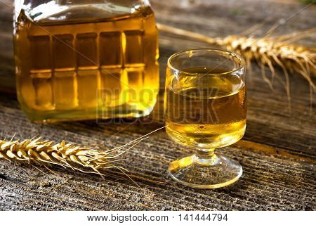 Glass Of Brandy Or Cognac And Bottle On  Wooden Table.