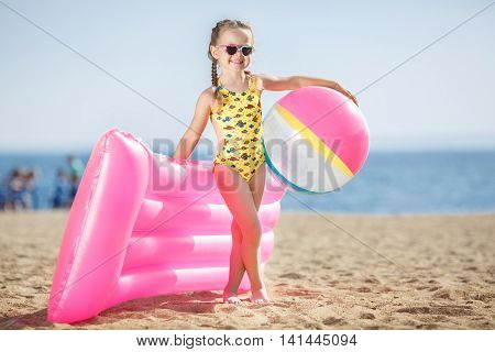 Little girl with pigtails,wearing sun glasses in the shape of hearts,dressed in a yellow swimsuit with colorful fishes,in the hands holding a large bouncy ball and a pink inflatable mattress,standing on a sandy beach on the ocean