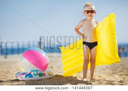 A little boy with short hair and blond hair, dark mirrored sun glasses, a dark blue panties,posing, single,standing on a sandy tropical beach with yellow inflatable mattress in his hands near the ball and lifebelt on the shore of the blue ocean