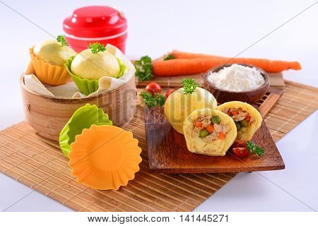 Chicken chinese dumplings with carrot sliced tomato and herbs on wooden bamboo tray
