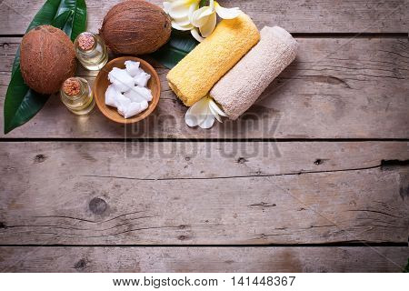 Coconuts coconut oil and towels on vintage wooden background. Spa setting. Natural organic spa products. Flat lay with copy space.
