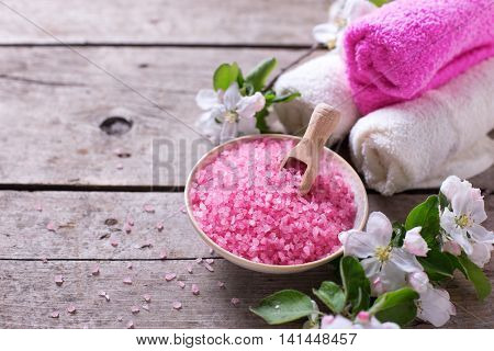 Spa or wellness organic product. Pink sea salt in bowl towels and apple tree flowers on aged wooden background. Selective focus.