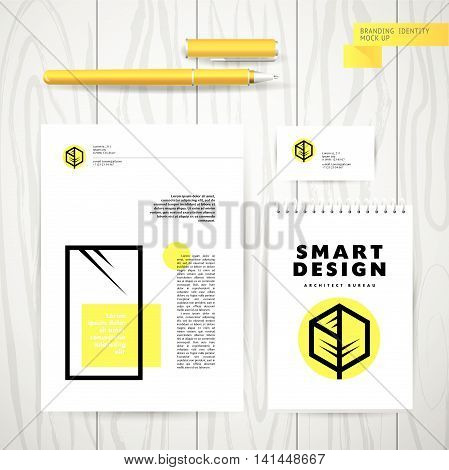 Vector architect studio logo design. Building construction company insignia isolated on wood texture table background. Product branding mock up. Blank letter paper sheet, notebook, pen, business card.