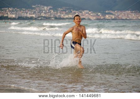 boy frolics in the sea with splashes and waves.
