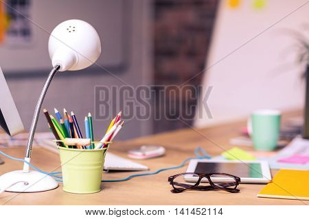 Digital tablet, spectacles and penholder on a table in office