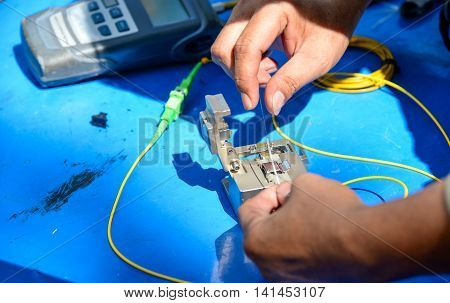 Technician useing cleaver cutting optic fiber on blue table with meter.