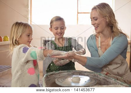Woman having fun with girls while making pottery in pottery workshop