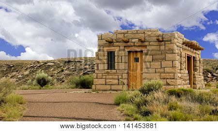 Desert brick adobe with sand rock and blue sky in the background