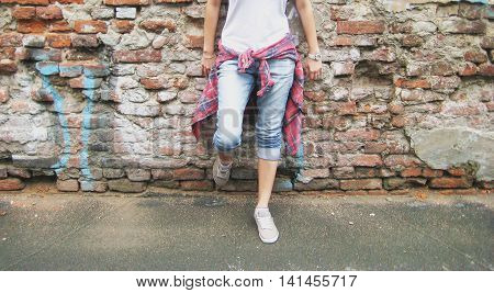 Lifestyle portrait of stylish young person in casual clothes: white t-shirt, plaid shirt, blue jeans and gray sneakers standing against urban brick wall background.