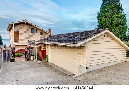 View Of Separate Garage With Concrete Driveway.