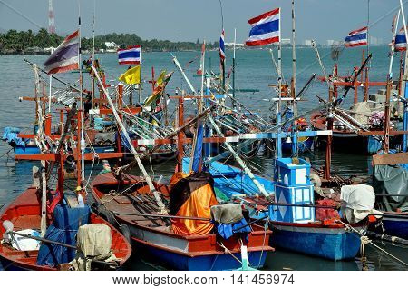 Hua Hin Thailand - December 30 2009: A fleet of wooden fishing boats flying the Thai flag moored in the shallow waters by the Hua Hin fishing pier