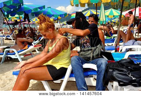 Phuket Thailand - January 9 2012: Young Thai tattoo artist with long hair applies a temporary henna star tattoo on the back of a Belgian visitor to Patong Beach