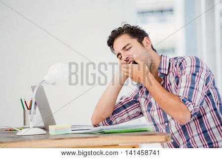 Young man yawning at his desk in the office