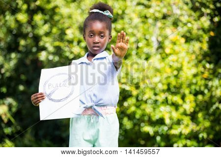 Cute mixed-race girl holding a message and saying stop with her hand on a park