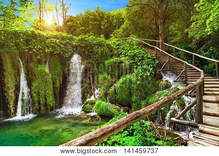 Amazing waterfall in Plitvice Lakes National Park Croatia Europe. Majestic view with turquoise water wooden handrail stairs and sunset sunny beams travel destinations background