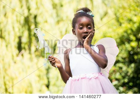 Cute mixed-race girl wearing a fairy dress on a park