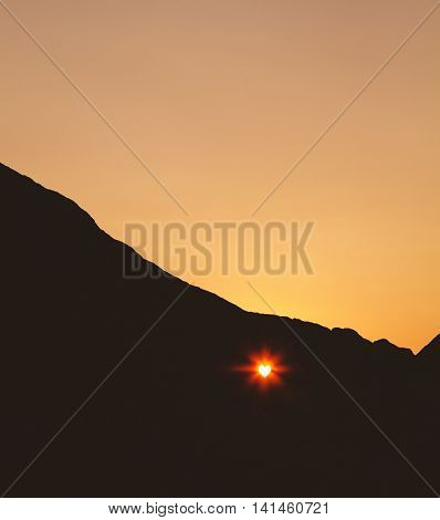 Sunet through the heartshaped hole in the cliff
