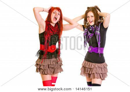 Two cute girlfriends with hands near head unhappily crying isolated on white