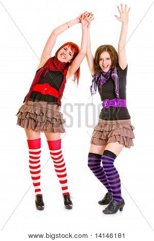 Two cute happy girlfriends standing with hands raised up isolated on white