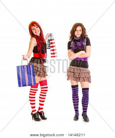 Pleased pretty girl showing shopping bags to her sad girlfriend isolated on white